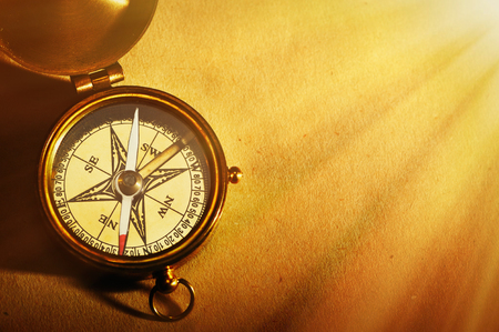 old fashioned: Antique brass compass over old paper background