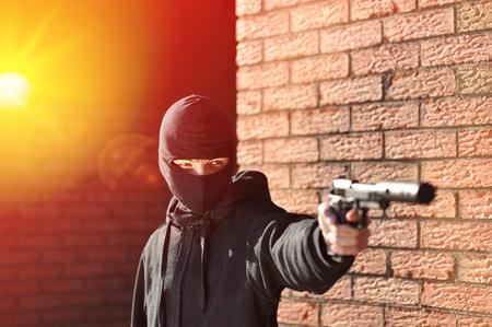 the silencer: Gunman in black mask holding gun with silencer