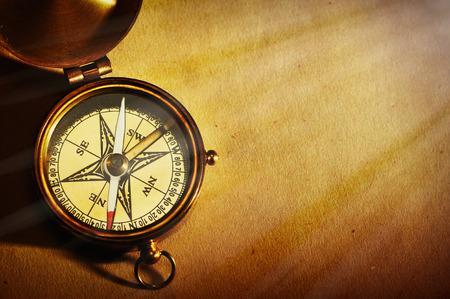 Antieke koperen kompas over oude-paper achtergrond