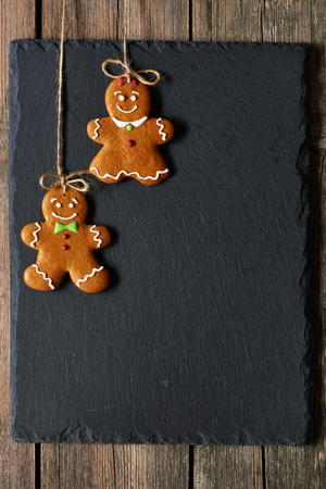 Christmas homemade gingerbread couple cookies over slate 写真素材