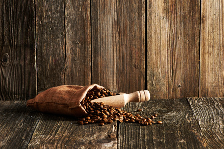 coffee sack: Coffee beans and scoop in sack on wooden table Stock Photo
