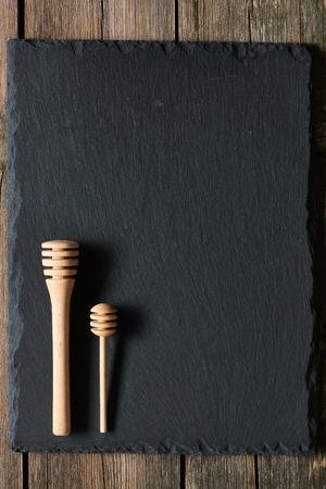 dipper: Wooden honey dipper on slate background Stock Photo