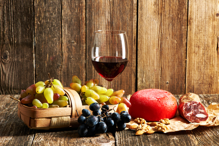 Fresh grapes, red wine and cheese on old wooden table