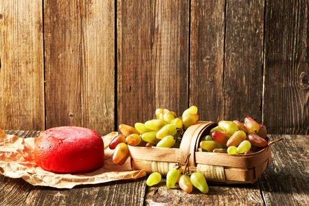 picnic food: Fresh grapes and cheese on old wooden table Stock Photo