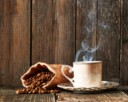 Cup of coffee and coffee beans in sack on wooden table Stockfoto