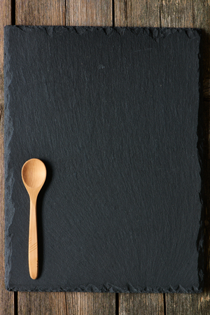 blank slate: Wooden spoon on slate background
