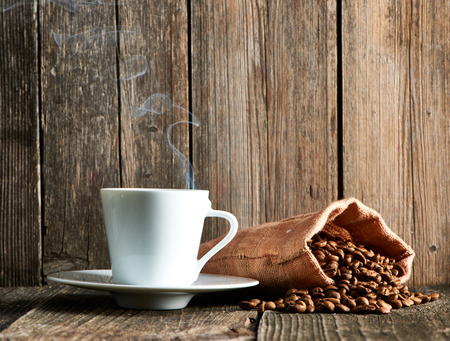 cups: Cup of coffee and coffee beans in sack on wooden table Stock Photo