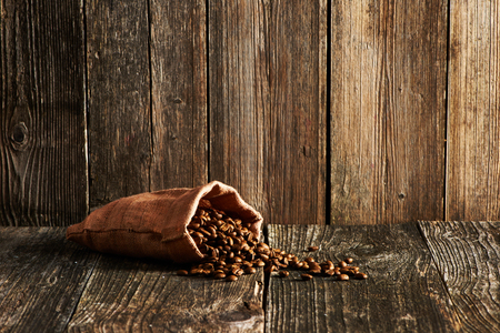 coffee sack: Coffee beans in sack on wooden table