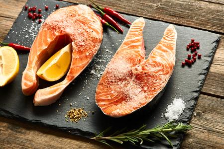 Raw salmon steaks and ingredients on slate background Standard-Bild