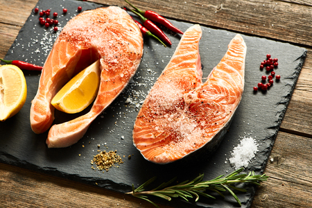 Raw salmon steaks and ingredients on slate background Stock Photo