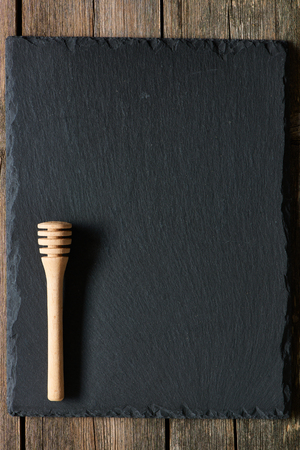 grunge cutlery: Wooden honey dipper on slate background Stock Photo