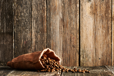 Coffee beans in sack on wooden table