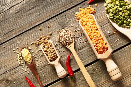 vegetarian food: Spoons of various legumes on wooden background
