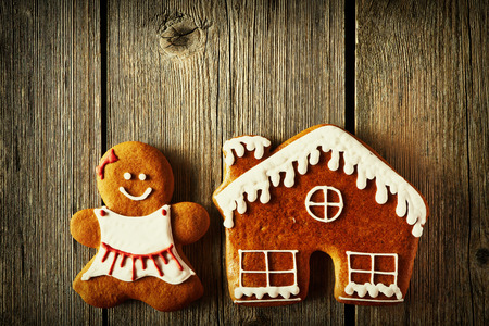 christmas house: Christmas homemade gingerbread girl and house on wooden table Stock Photo
