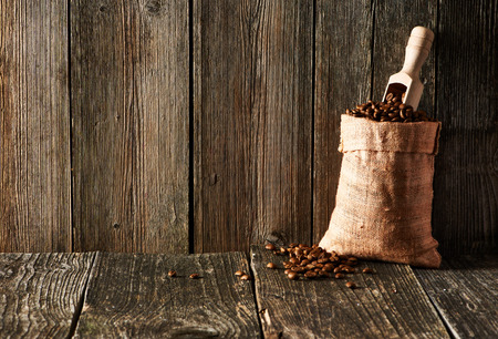 Coffee beans and scoop in sack on wooden table Imagens