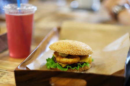 food tray: Cheeseburger on sesame buns and drink