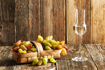 grappa: Fresh grapes and glass of grappa on old wooden table
