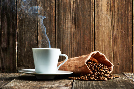 Cup of coffee and coffee beans in sack on wooden table Imagens