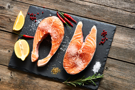 fruit background: Raw salmon steaks and ingredients on slate background Stock Photo