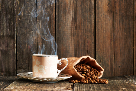 coffee sack: Cup of coffee and coffee beans in sack on wooden table Stock Photo