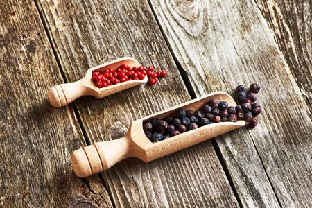 frutas deshidratadas: Cucharas de madera con bayas de enebro secas y pimienta rosa sobre fondo rústico