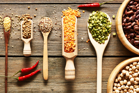 pea: Bowls and spoons of various legumes on wooden background