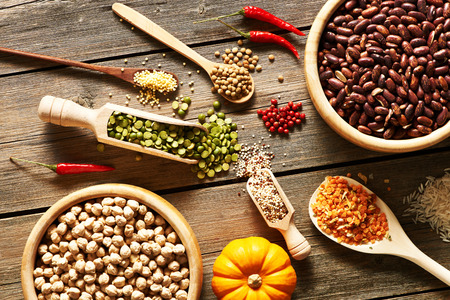 black beans: Bowls and spoons of various legumes on wooden background