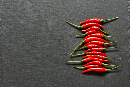 chili pepper: Red hot chili peppers on slate background