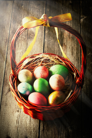 wooden basket: Colored easter eggs in basket on wooden table Stock Photo