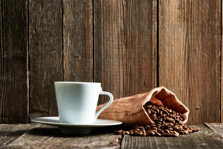 filiżanka kawy: Filiżanka kawy i ziarna kawy w worek na drewnianym stole Zdjęcie Seryjne