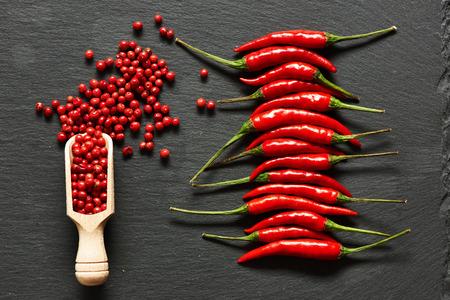 pepe nero: peperoni rossi hot chili e pepe rosa su sfondo di ardesia
