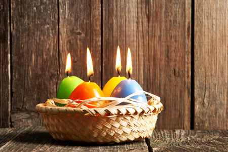 easter candle is burning: Easter candles in egg form on old wooden table