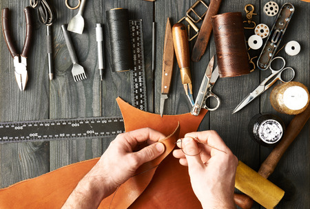 Man working with leather using crafting DIY tools Stock Photo