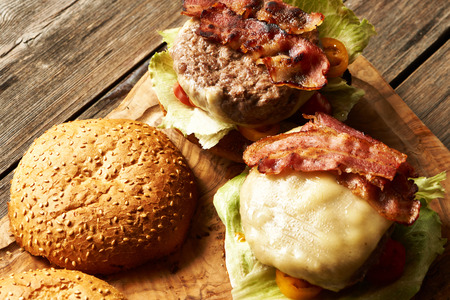 cheeseburgers: Home made cheeseburgers on rustic wooden table