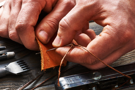 Man working with leather using crafting DIY tools Banco de Imagens