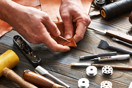 Man working with leather using crafting DIY tools Фото со стока