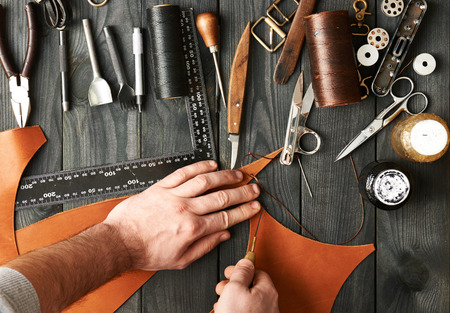 wood craft: Man working with leather using crafting DIY tools Stock Photo