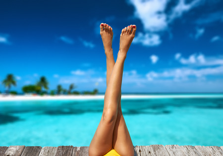 女性のビーチの桟橋でリラックス