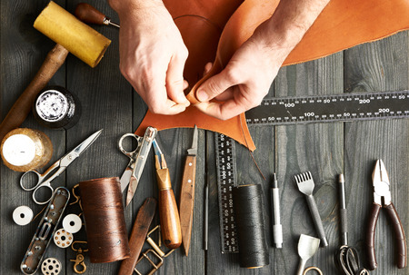 leather background: Man working with leather using crafting DIY tools Stock Photo