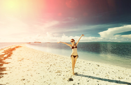 petite fille maillot de bain: Jeune fille sur une plage tropicale avec bras étendus