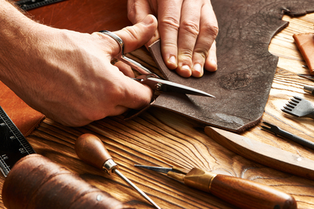 Man working with leather using crafting DIY tools 免版税图像