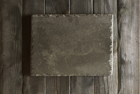 texture backgrounds: Empty slate plate over black wooden background