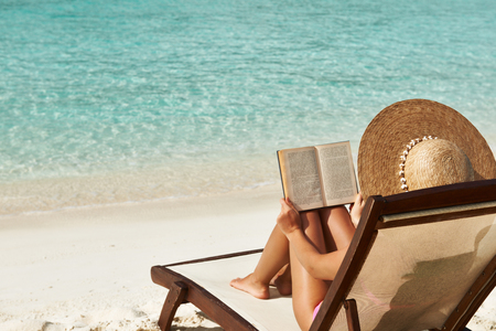 Young woman reading a book at the beach 스톡 콘텐츠