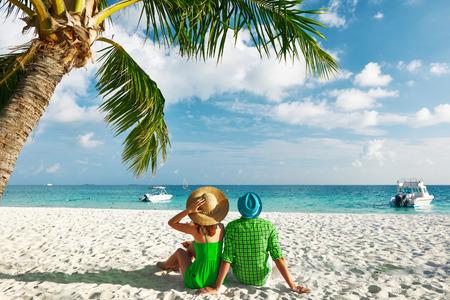 luna de miel: Pareja en ropa verde en una playa tropical en Maldivas Foto de archivo