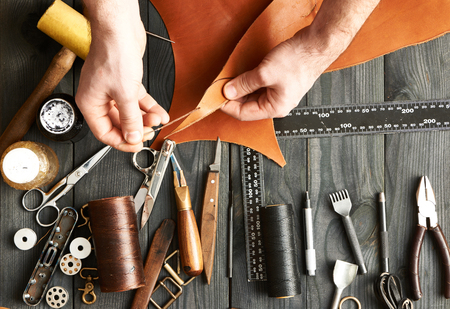 hand tool: Man working with leather using crafting DIY tools Stock Photo