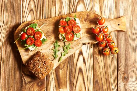 bocadillo: saludables bocadillos vegetales con pan de grano entero, puré de garbanzos y tomates Foto de archivo