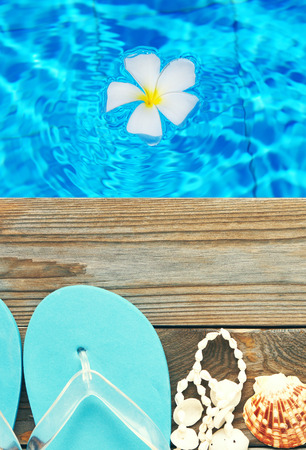wooden shoes: Flip-flops by a swimming pool Stock Photo