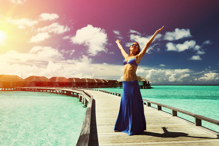 jetty: Woman on a tropical beach jetty at Maldives Stock Photo