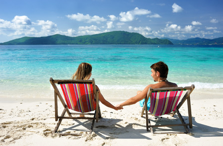 bikini couple: Couple on a tropical beach in chaise lounge