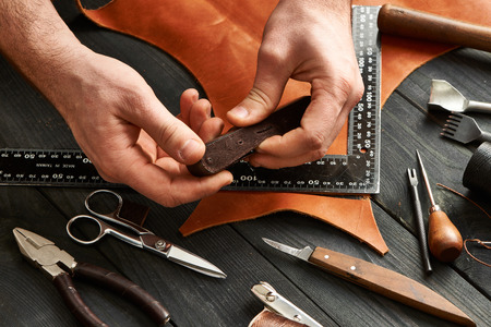 craft product: Man working with leather using crafting DIY tools Stock Photo